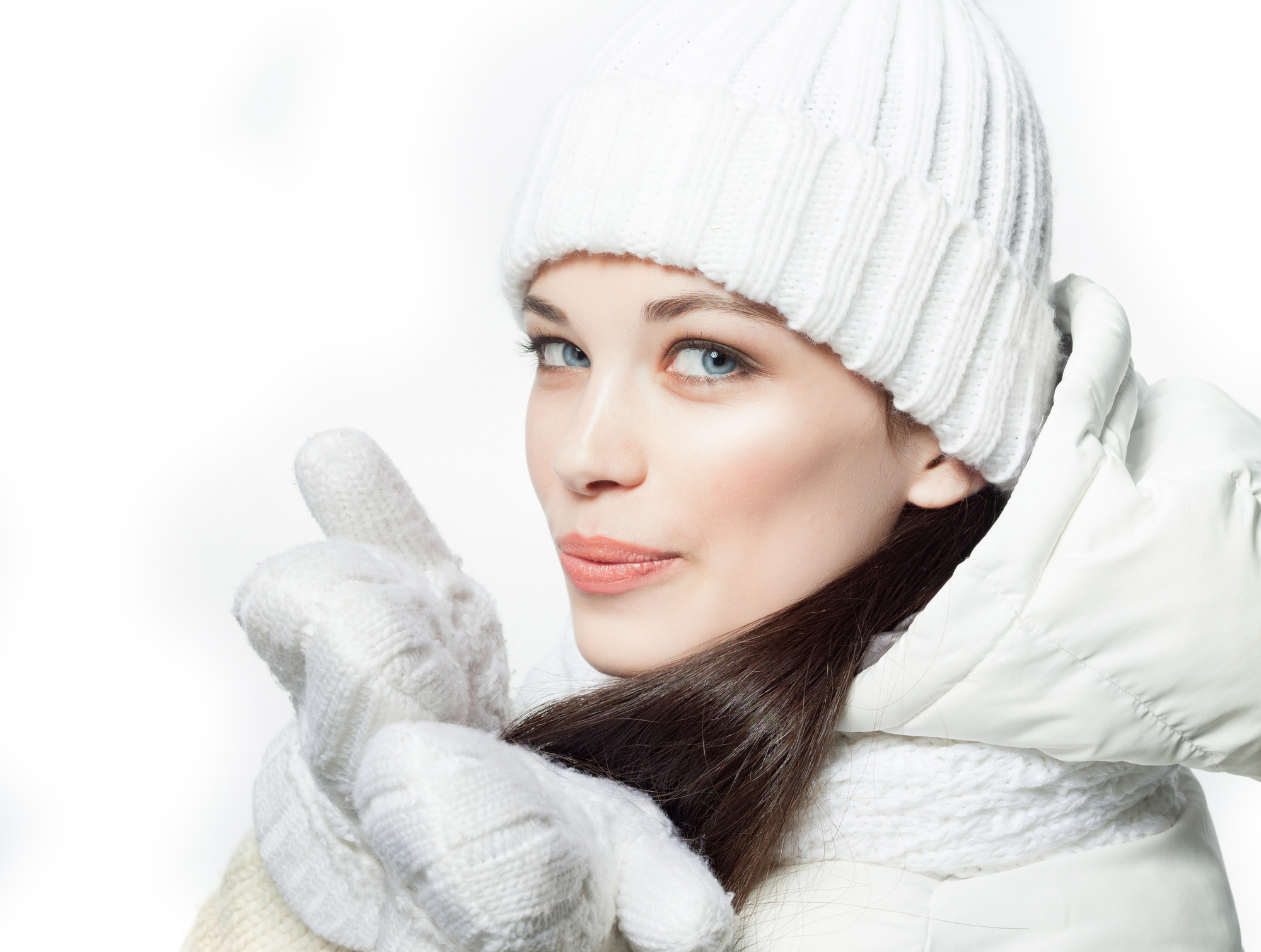closeup portrait of attractive caucasian smiling woman brunette isolated on white studio shot lips face hair head and shoulders looking at camera warm clothing winter cristmas